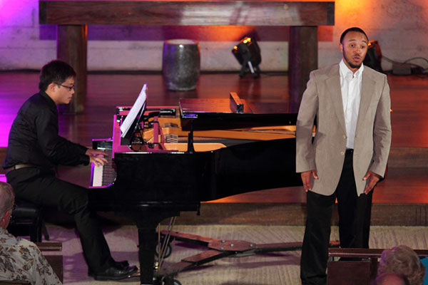 piano player and male singer on stage